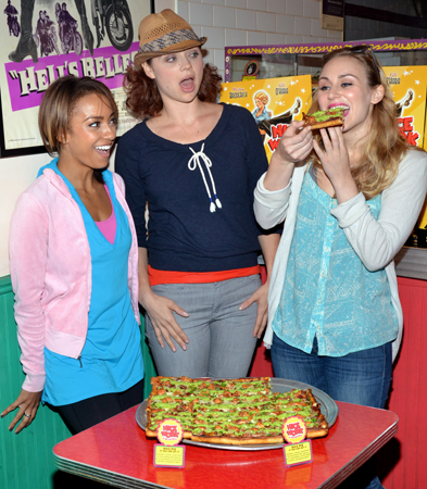 "Shina Morris and Kristen Beth Williams look on as Stephanie Martignetti takes a bite out of the new Two Boots pizza, titled ""Nice Pie If You Can Get It"""