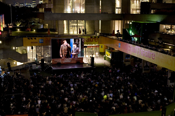 An audience gathers to watch NTL's live broadcast of <i>One Man, Two Guvnors</i> outside London's National Theatre.