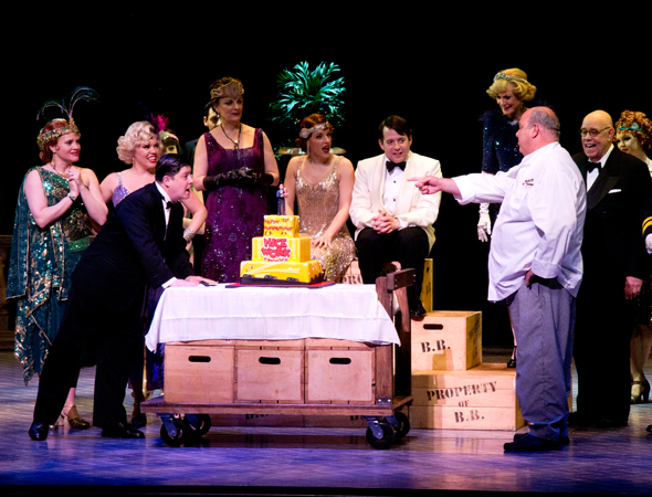 Tony Award winner Michael McGrath, who plays the role of bootlegger Cookie McGee, listens as Chef Mauro Castano of Carlo's Bakery explains the process of creating the cake. <br />(© David Gordon)