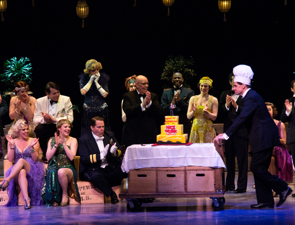 As an excited cast looks on, Broadway veteran Michael X. Martin, who played the role of Duke Mahoney at the performance, wheels on the celebratory anniversary cake.<br />(© David Gordon)