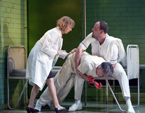 Jenny Sterlin (left) and Brendan Titley (right) tend to Alan Cumming (center) in <i>Macbeth</i>.