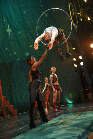 Leading Player Patina Miller watches the high-flying Philip Rosenberg alongside company members Viktoria Grimmy and Orion Griffiths <br />© Joan Marcus
