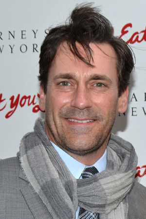 A windblown Jon Hamm smiles on his way into the Booth Theatre.<br />(© David Gordon)