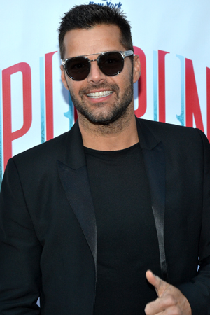 Rocking a pair of sunglasses, recent <i>Evita</i> star Ricky Martin flashes us a thumbs up on his way into the Music Box Theatre.<br />(© David Gordon)