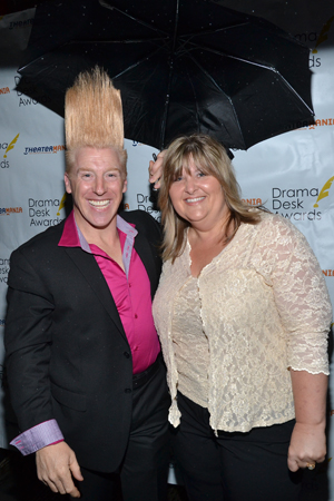 Clown extraordinaire Bello shields his wife and considerable hair from the rain. He is nominated in the Unique Theatrical Experience this evening for <I>Bello Mania</I>.   <br />(© David Gordon)
