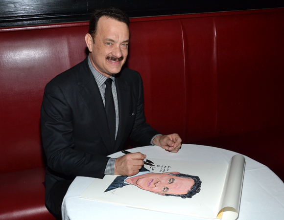 Tom Hanks autographs his brand new caricature.