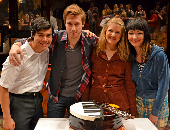 New cast members Carlos Valdes, Arthur Darvill, Joanna Christie, and Katrina Lenk smile alongside the production's 500th performance cake, designed by The Chocolate Swirl.<br />(© David Gordon)