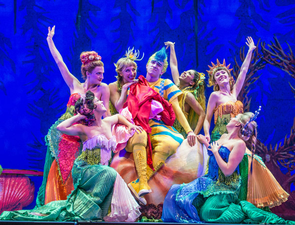 Christian Probst (center) as the lovable Flounder with his ensemble of mermaids. <br />(© Billy Bustamante)