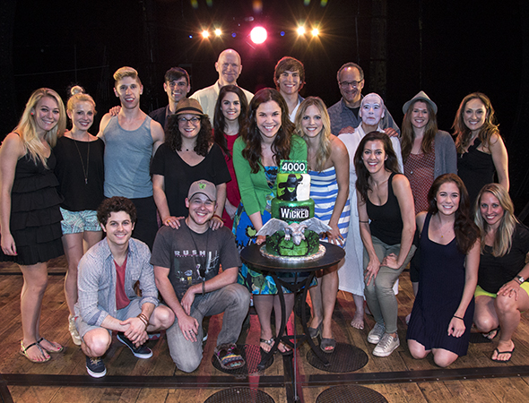 The cast of <i>Wicked</i> with the celebratory cake from The Chocolate Swirl.<br />(© David Gordon)