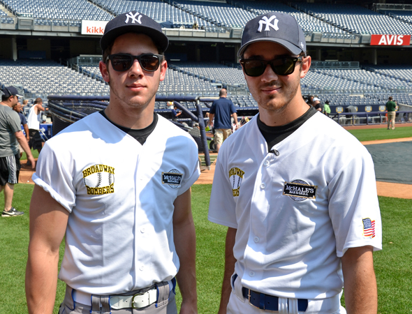 Not only do Jonas Brothers Nick and Kevin sing and act, but they also play a mean game of softball.<br />(© David Gordon)