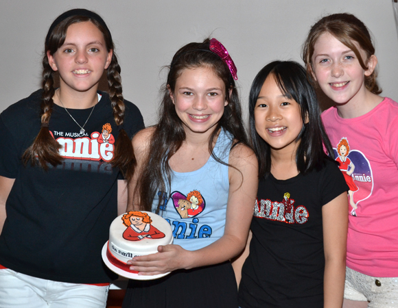 <i>Annie</i> stars Georgi James, Madi Rae DiPietro, Junah Jang, and Jaidyn Young show off the musical's specially designed cake.