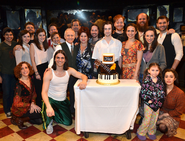 The <i>Once</i> family celebrates a milestone with a cake partially shaped like a guitar.<br />(© David Gordon)
