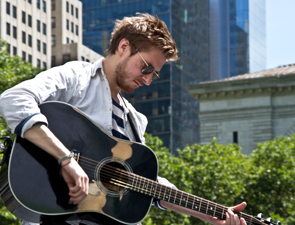 Arthur Darvill tunes up his guitar.<br />(© David Gordon)