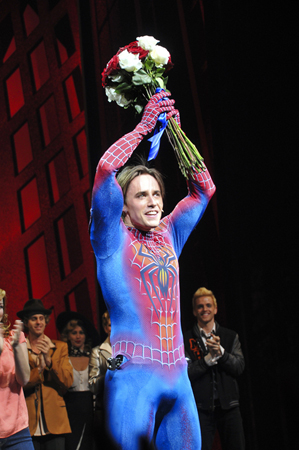 Carney receives a celebratory bouquet of flowers — and raises them to the sky.<br />(© Jenny Anderson/SPIDER-MAN Turn Off The Dark)