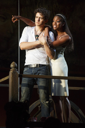 Orlando Bloom (Romeo) and Condola Rashad (Juliet) cuddle on the balcony.<br />(© Carol Rosegg)