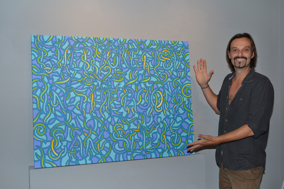 Julien Havard posing with his artwork at Taglialatella Galleries.